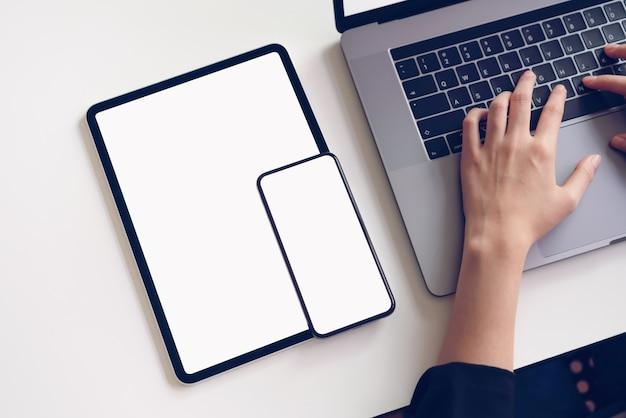 Geschäftsfrau, die auf tastaturlaptop und digitaler tablette schreibt