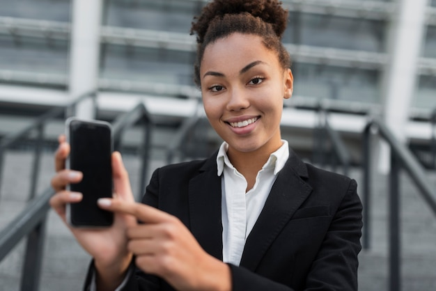 Geschäftsfrau, die auf telefon zeigt
