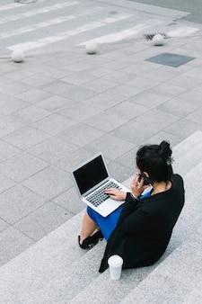 Geschäftsfrau, die auf treppenhaus unter verwendung des laptops sitzt und auf mobiltelefon spricht