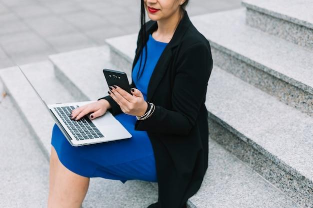 Geschäftsfrau, die auf treppenhaus unter verwendung des laptops und des smartphone sitzt