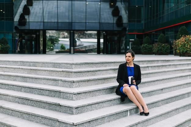 Geschäftsfrau, die auf treppenhaus vor gebäudeeingang sitzt