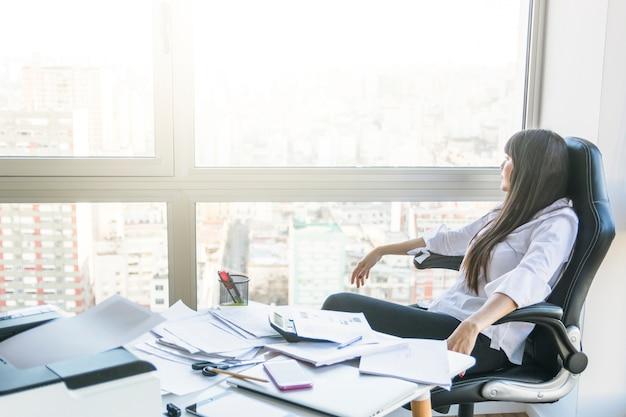 Geschäftsfrau, die aus dem fenster heraus sitzt im büro schaut