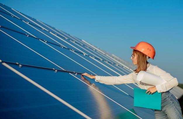 Geschäftsfrau, die ausrüstung im solarkraftwerk mit tablet-checkliste prüft