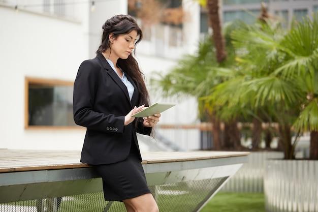 Geschäftsfrau, die außerhalb des bürogebäudes arbeitet