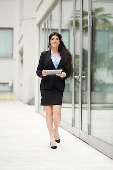Geschäftsfrau, die außerhalb des bürogebäudes mit digitalen geräten arbeitet