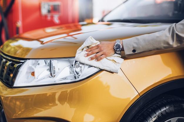 Geschäftsfrau, die auto an der autowaschanlage wäscht.