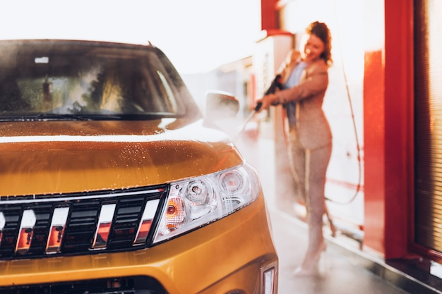 Geschäftsfrau, die auto an der autowaschstation mit hochdruckwassermaschine wäscht.