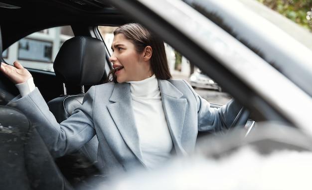 Geschäftsfrau, die auto fährt, genervt nach hinten schaut und sich beschwert.