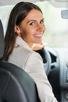 Geschäftsfrau, die auto fährt. rückansicht einer selbstbewussten jungen geschäftsfrau, die auto fährt und über die schulter schaut