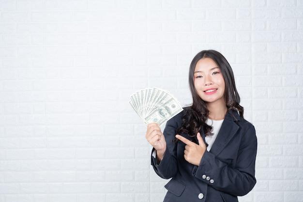 Geschäftsfrau, die banknote, bargeld separat hält, weiße backsteinmauer machte gesten mit gebärdensprache.