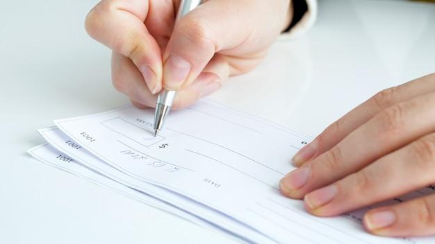 Geschäftsfrau, die bankscheck am schreibtisch ausfüllt und unterschreibt.