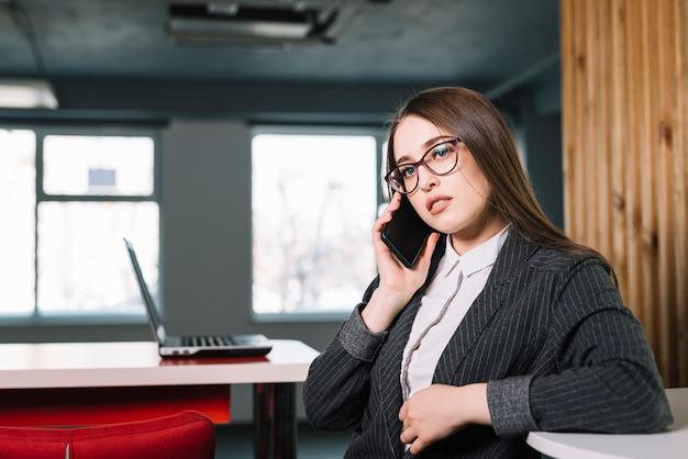 Geschäftsfrau, die bei tisch telefonisch spricht