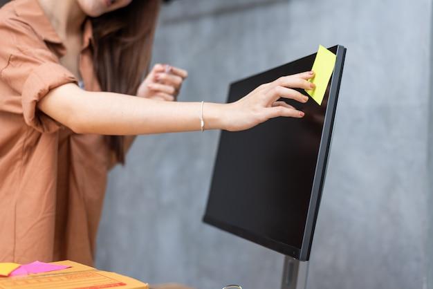 Geschäftsfrau, die bestellungslistenmemo auf dem bildschirm für das erinnern setzt, um pakete zu senden