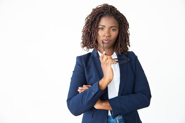 Geschäftsfrau, die brillen hält und kamera betrachtet