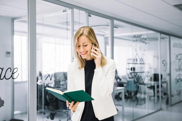 Geschäftsfrau, die buch anruft und untersucht