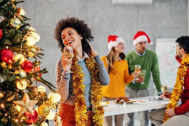 Geschäftsfrau, die champagner am heiligabend in ihrer firma hält. im hintergrund sind ihre kollegen.