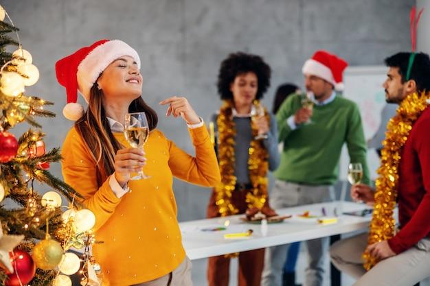 Geschäftsfrau, die champagner hält, neben weihnachtsbaum steht und silvester feiert.