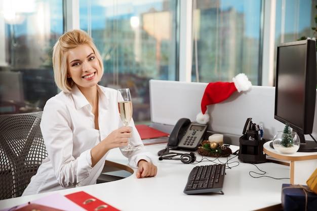 Geschäftsfrau, die champagner lächelnd im büro am weihnachtstag sitzt.
