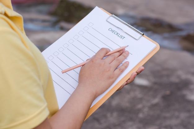 Geschäftsfrau, die checkliste am schreibtisch vorbereitet