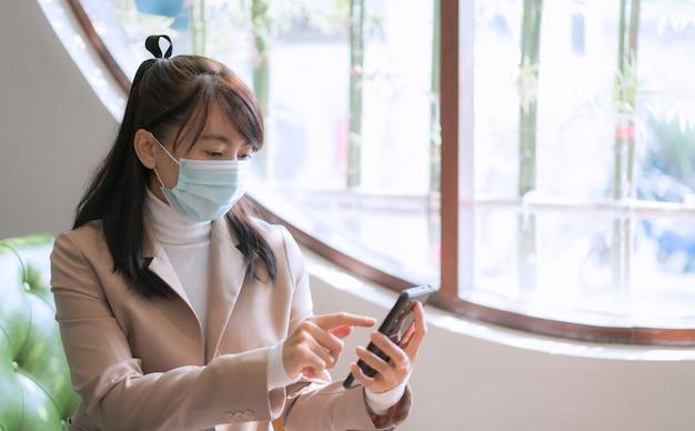 Geschäftsfrau, die chirurgische maske trägt und smartphone für arbeit, soziale medien verwendet