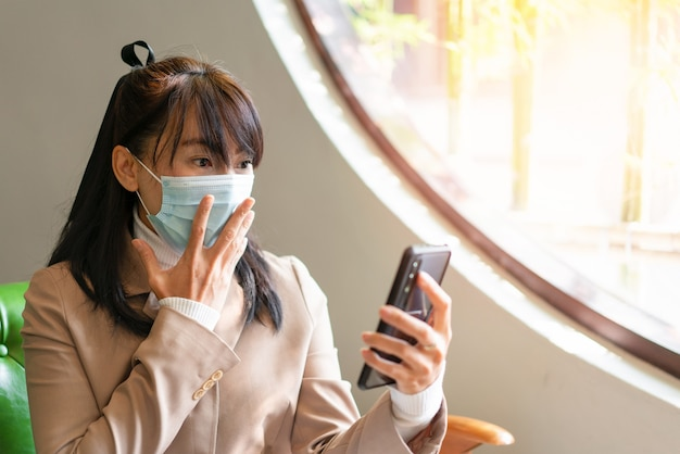 Geschäftsfrau, die chirurgische maske trägt und smartphone für die arbeit in sozialen medien verwendet