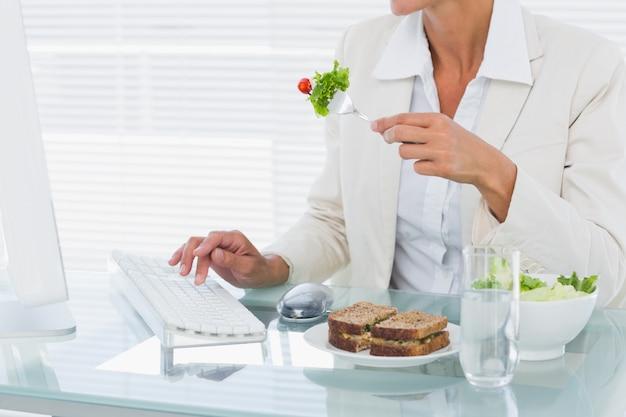 Geschäftsfrau, die computer beim essen des salates am schreibtisch verwendet