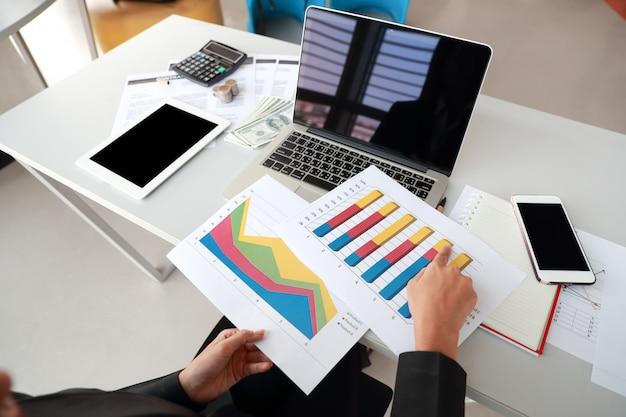 Geschäftsfrau, die computer, tablette verwendet und mit zusammenfassendem bericht der diagrammfirma arbeitet