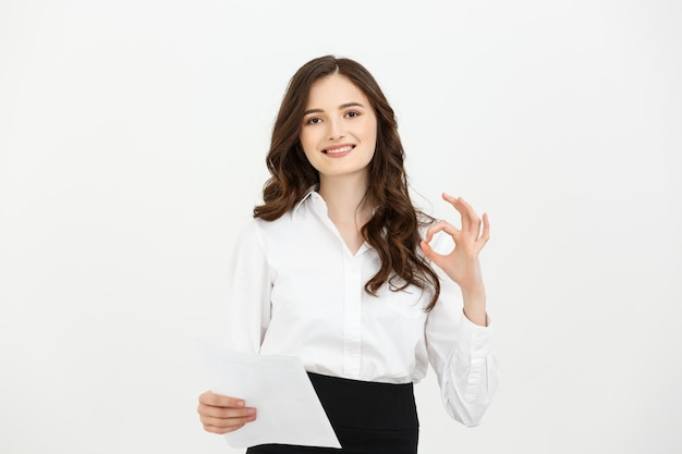 Geschäftsfrau, die das okhandzeichenlächeln glücklich zeigt.