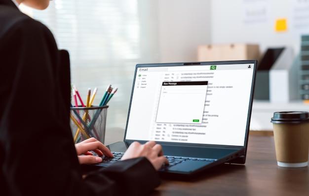 Geschäftsfrau, die das schreiben einer nachricht online e-mail auf laptop auf dem tisch im büro tippt.
