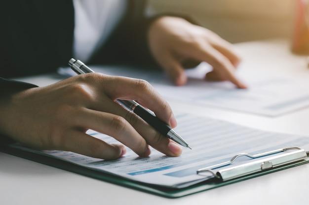 Geschäftsfrau, die daten in finanzdiagrammen und -graphen überprüft. geschäftsfinanzierung rechnungswesen bankkonzept