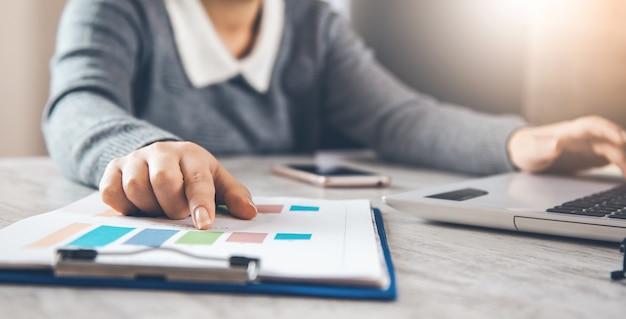 Geschäftsfrau, die daten in finanzdiagrammen und -graphen überprüft