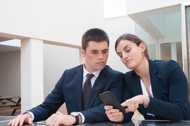 Geschäftsfrau, die dem mitarbeiter informationen über telefonbildschirm zeigt