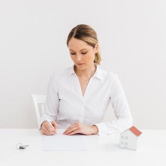 Geschäftsfrau, die den dokumentenvertrag eines verkaufs für ein neues haus unterzeichnet