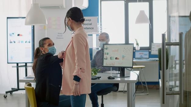 Geschäftsfrau, die den ellbogen berührt, um die soziale distanzierung zu respektieren, um viruserkrankungen zu verhindern. mitarbeiter mit gesichtsmasken, die während der coronavirus-pandemie im büro des unternehmens arbeiten