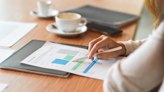 Geschäftsfrau, die den finanzbericht liest, während sie den stylus-stift auf dem holzschreibtisch mit tablet hält?