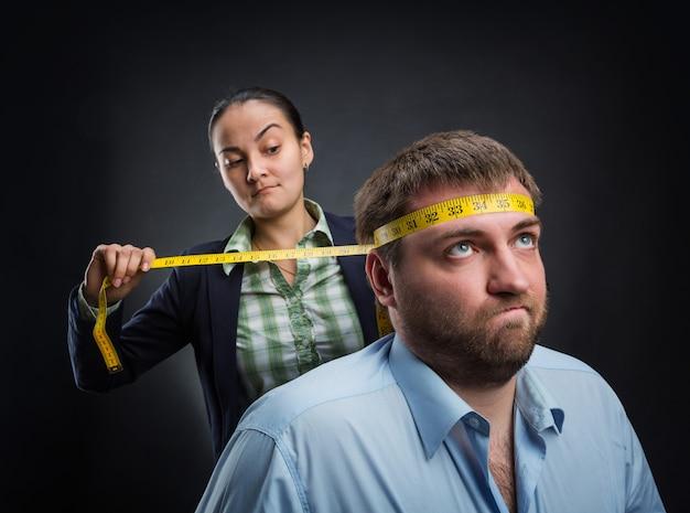 Geschäftsfrau, die den kopf des mannes mit meterstab misst