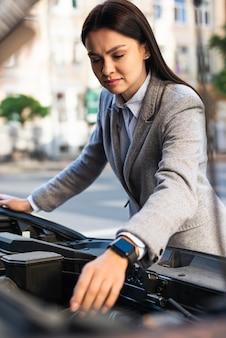 Geschäftsfrau, die den motor des autos prüft