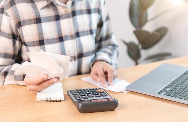 Geschäftsfrau, die den rechner drückt, berechnet die verschiedenen kosten, die durch die gehaltenen und auf den tisch gelegten rechnungsrechnungen bezahlt werden müssen.