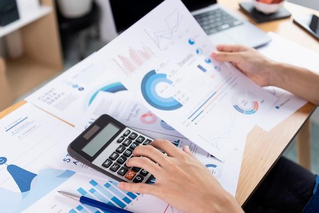 Geschäftsfrau, die den taschenrechner verwendet, der das analysedokumentdiagramm des unternehmensfinanzstrategiestatistik-erfolgskonzepts und die planung für die zukunft im büroraum überprüft.