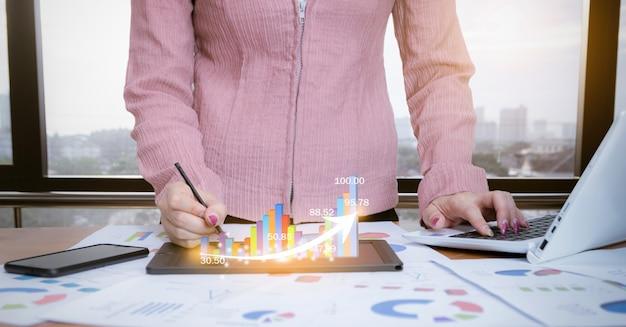 Geschäftsfrau, die diagramme mit computertechnologiesozialen netzwerken analysiert