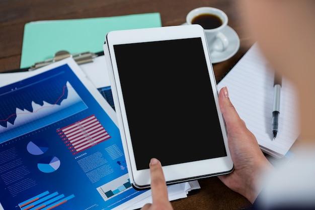 Geschäftsfrau, die digitales tablett mit diagramm auf tabelle verwendet