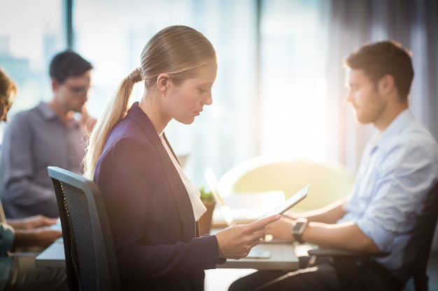 Geschäftsfrau, die digitales tablett während des treffens verwendet
