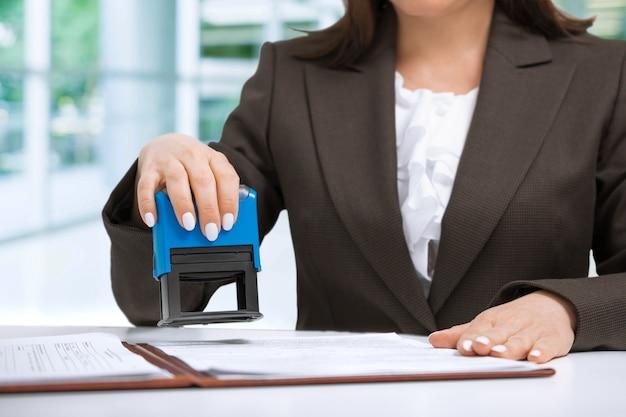 Geschäftsfrau, die dokumente im büro stempelt