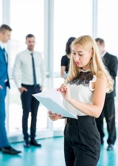 Geschäftsfrau, die dokumente mit ihren kollegen im hintergrund analysiert