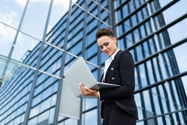 Geschäftsfrau, die draußen mit laptop arbeitet