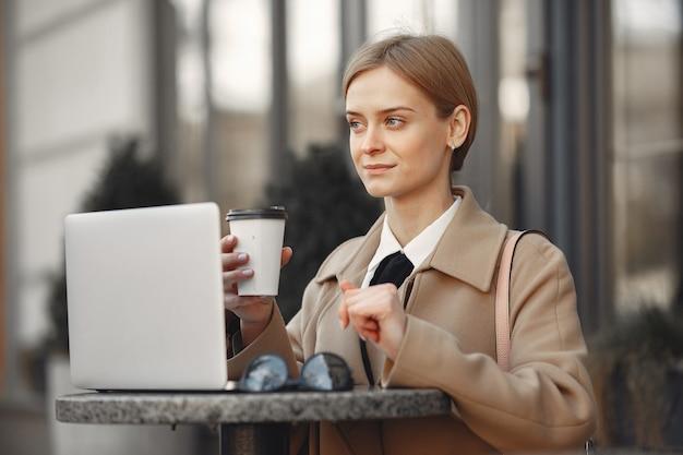 Geschäftsfrau, die draußen mit laptop und kaffee steht