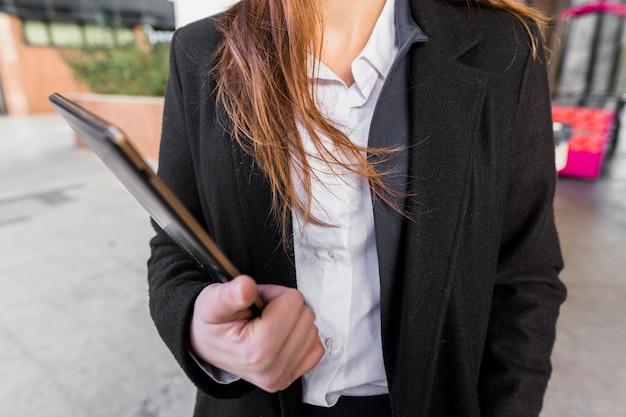 Geschäftsfrau, die draußen mit tablette steht