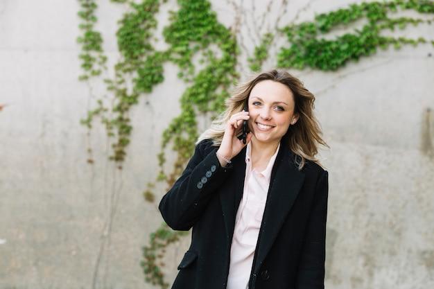Geschäftsfrau, die draußen telefonanruf macht