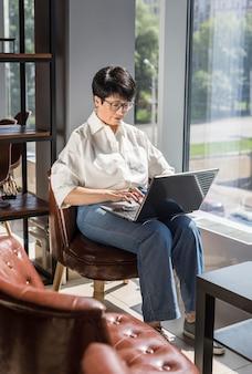 Geschäftsfrau, die drinnen an ihrem laptop arbeitet