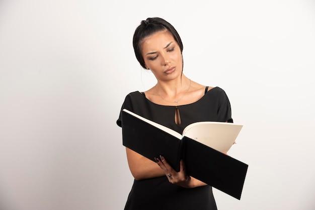 Geschäftsfrau, die durch das notizbuch auf der weißen wand schaut.